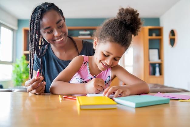 Moeder helpt en ondersteunt haar dochter met homeschool terwijl ze thuis blijft. nieuw normaal levensstijlconcept. Gratis Foto