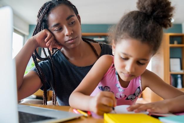 Moeder helpt en ondersteunt haar dochter met online school terwijl ze thuis blijft. nieuw normaal levensstijlconcept. monoparentaal concept. Gratis Foto