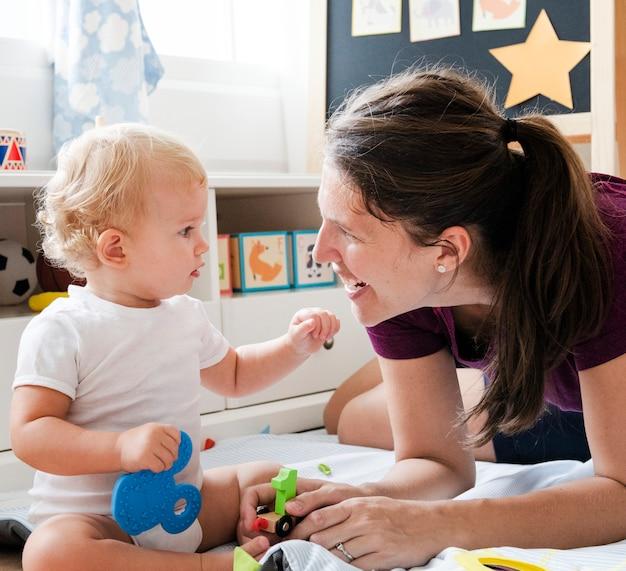 Moeder het spelen met haar baby op de vloer Premium Foto
