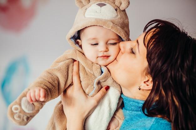 Moeder houdt haar zoontje in berenpak vast Premium Foto
