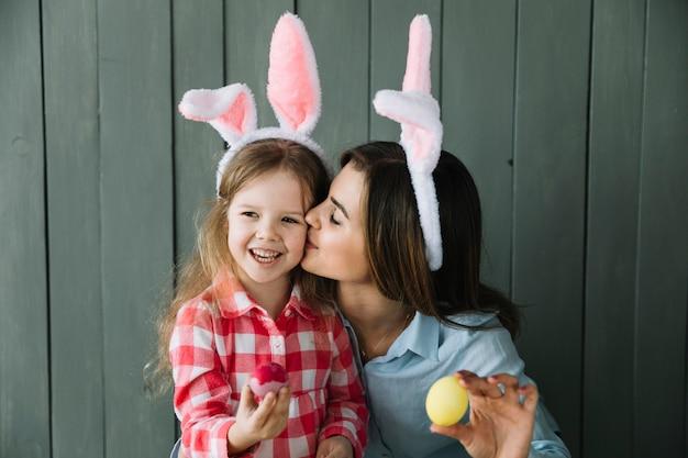 Moeder in konijntjesoren die dochter op wang kussen Gratis Foto