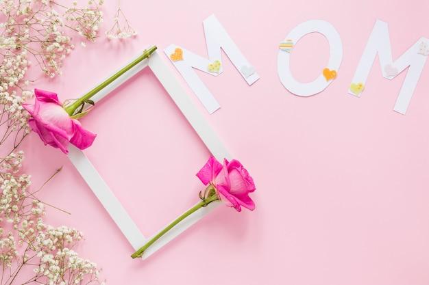 Moeder inscriptie met frame en rozen op tafel Gratis Foto