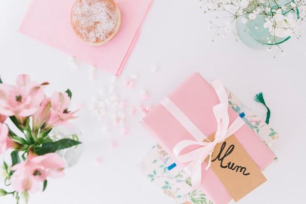 Moeder inscriptie met geschenkdoos, bloemen en donut Gratis Foto