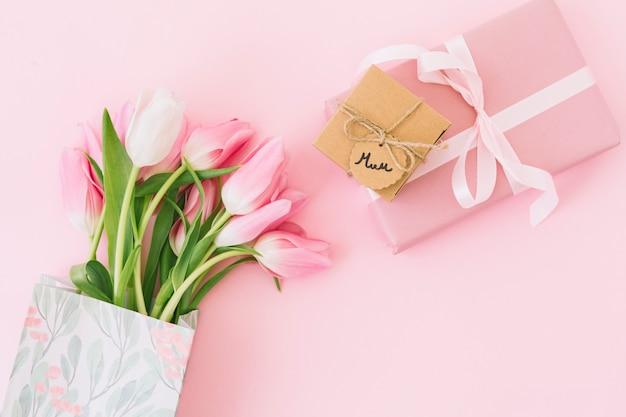 Moeder inscriptie met tulpen en geschenkdoos Gratis Foto