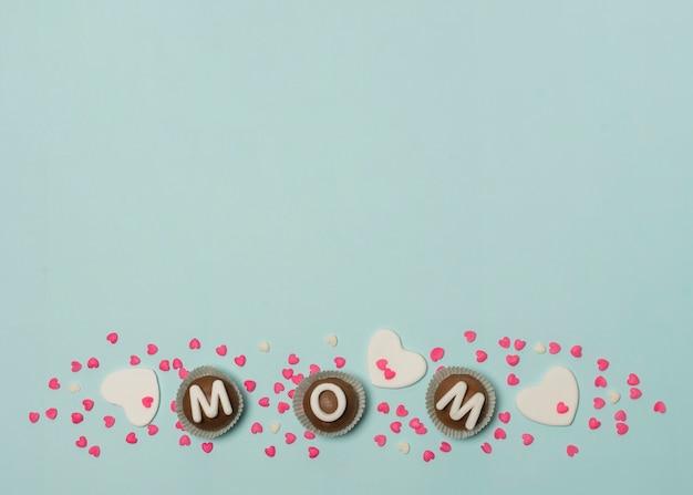 Moeder inscriptie op set van snoepjes tussen decoraties Gratis Foto