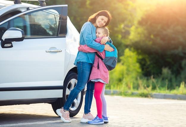Moeder knuffelen schoolmeisje na lessen over parkeren Premium Foto