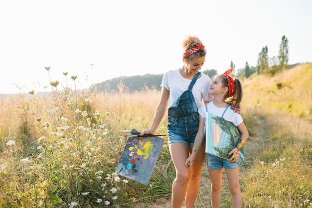 Moeder leert dochter verf in park. zonnige natuur, moeder en dochter schilderen een foto in een park, schilderen een klein kind, kindercreativiteit. Premium Foto