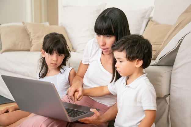 Moeder leert kinderen om laptop te gebruiken, hand van zoontje vast te houden en toetsenbordknop met jongensvinger in te drukken. Gratis Foto