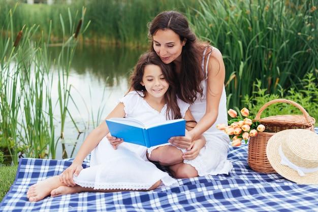 Moeder leesboek aan haar dochter bij het meer Gratis Foto