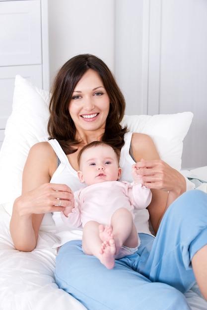 Moeder met baby om thuis te zitten in casuals Gratis Foto