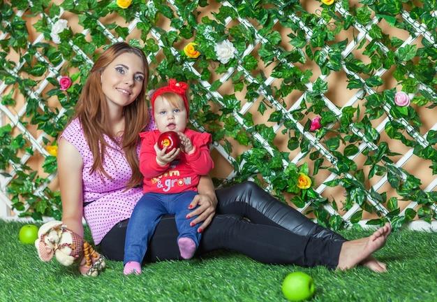 Moeder met baby op handzitting op het gras in de bloementuin Premium Foto
