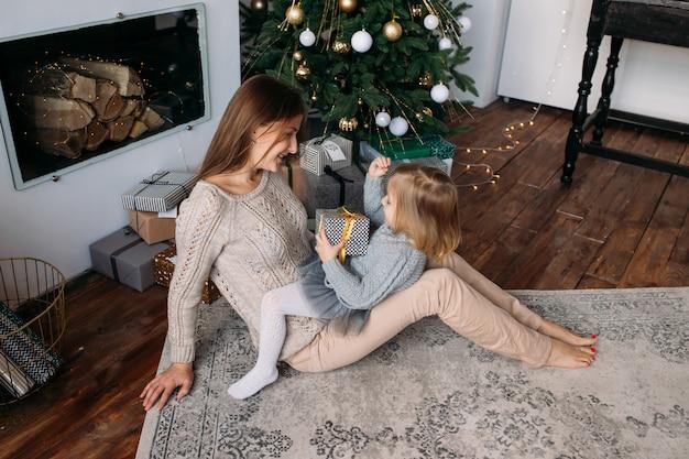 Moeder met dochter dichtbij kerstboom thuis Premium Foto