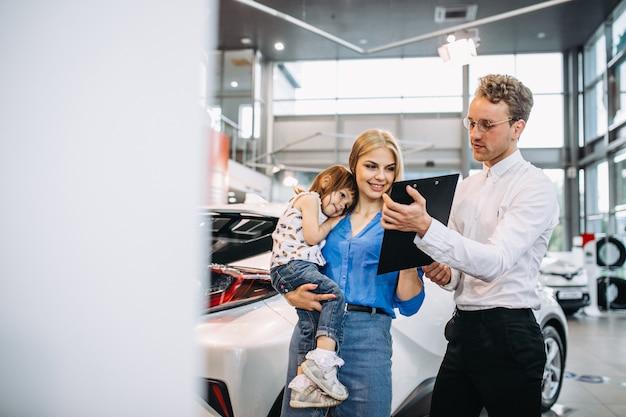 Moeder met dochter die aan verkoper in een autotoonzaal spreekt Gratis Foto