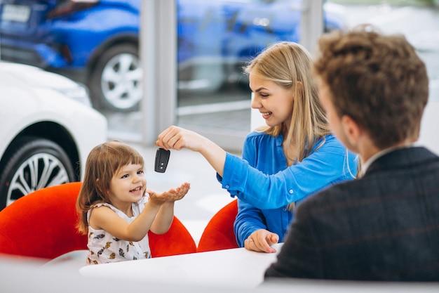 Moeder met dochter die een auto in een autotoonzaal koopt Gratis Foto