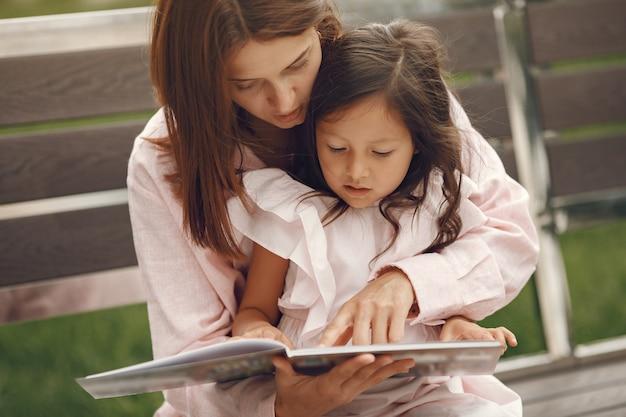 Moeder met dochter die een boek in de stad lezen Gratis Foto