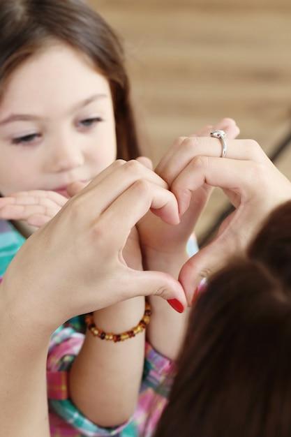 Moeder met dochter die harten met hun handen maakt Gratis Foto