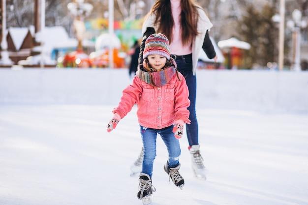 Moeder met dochter die het schaatsen op een piste onderwijzen Gratis Foto