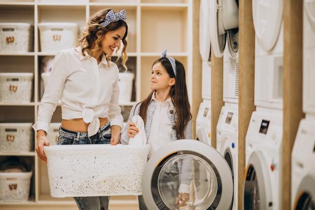 Moeder met dochter die wasserij doet bij zelfbedieningswasserette Gratis Foto