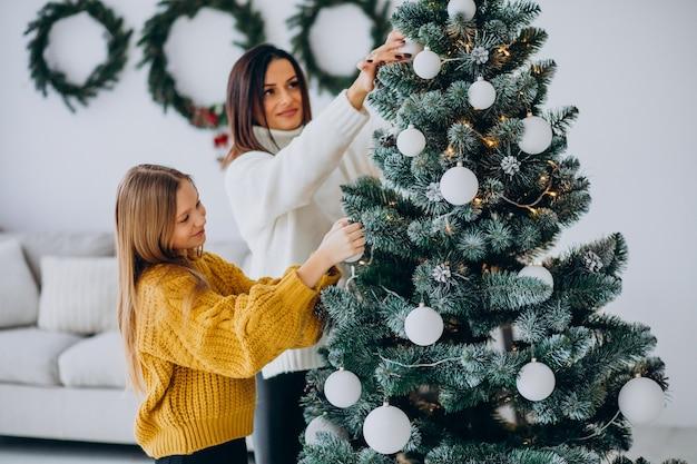 Moeder met dochter kerstboom versieren Gratis Foto