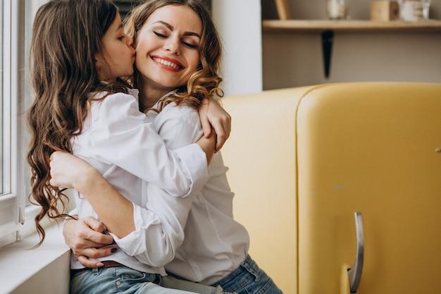 Moeder met dochter zitten in de keuken Gratis Foto