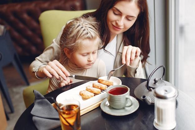 Moeder met dochter zitten in een café Gratis Foto