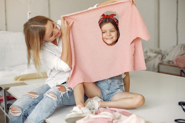 Moeder met dochtertje meet de te naaien stof Gratis Foto