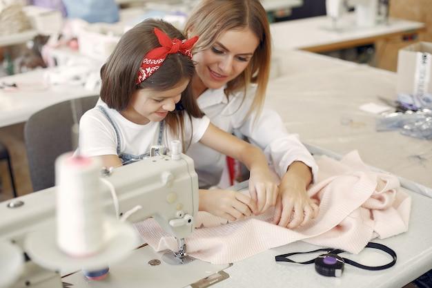 Moeder met dochtertje naait kleding in de fabriek Gratis Foto
