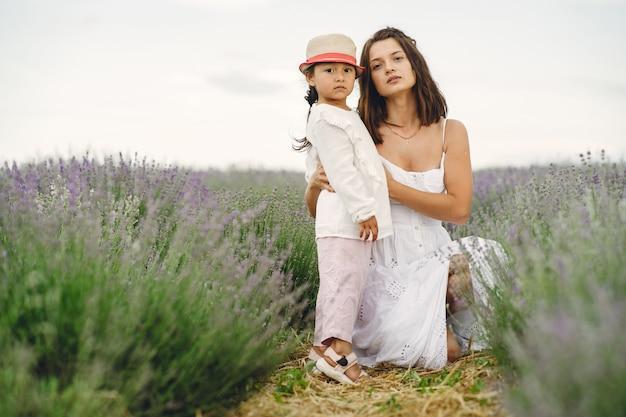 Moeder met dochtertje op lavendelveld. mooie vrouw en schattige baby spelen in weide veld. gezinsvakantie in zomerdag. Gratis Foto
