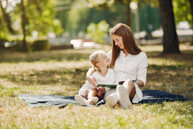 Moeder met dochtertje zittend op een plaid en lees het boek Gratis Foto