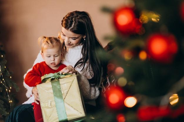 Moeder met dochterzitting door de kerstboom Gratis Foto