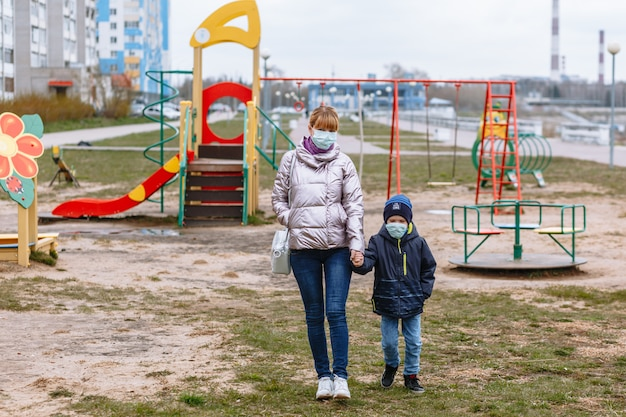 Moeder met een kind op de speelplaats, in medische maskers Premium Foto