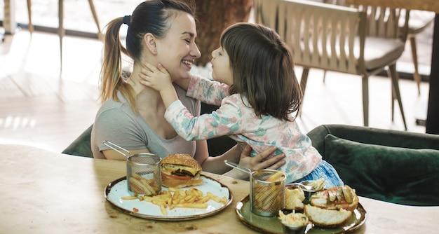 Moeder met een schattige dochter fastfood eten in een café Gratis Foto