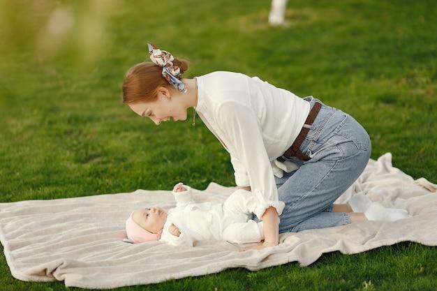 Moeder met haar baby tijd doorbrengen in een zomertuin Gratis Foto