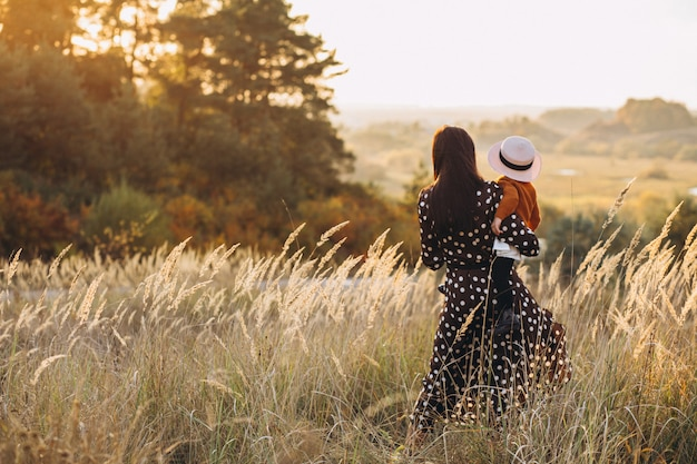 Moeder met haar babymeisje op een de herfstgebied Gratis Foto