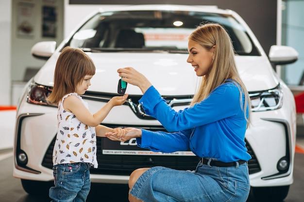 Moeder met haar dochtertje dat voor een auto staat Gratis Foto