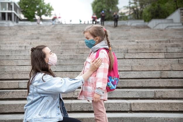 Moeder met haar dochtertje, een schoolmeisje, op de trap op weg naar school. coronavirus pandemie onderwijsconcept. Gratis Foto