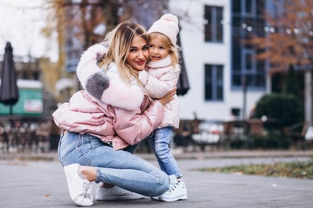Moeder met haar dochtertje gekleed in warme doek buiten de straat Gratis Foto