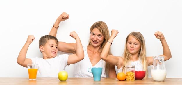 Moeder met haar twee kinderen die ontbijt hebben en overwinningsgebaar maken Premium Foto