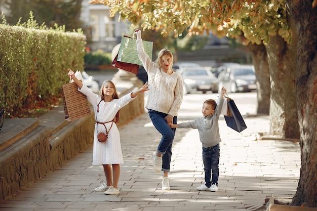 Moeder met kind met boodschappentas in een stad Gratis Foto