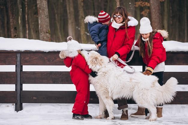 Moeder met kinderen en hond buiten spelen in de winter Gratis Foto