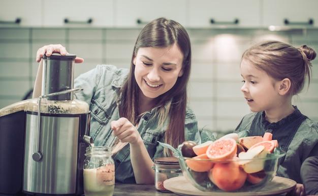 Moeder met kinderen in de keuken bereidt vers sap Premium Foto