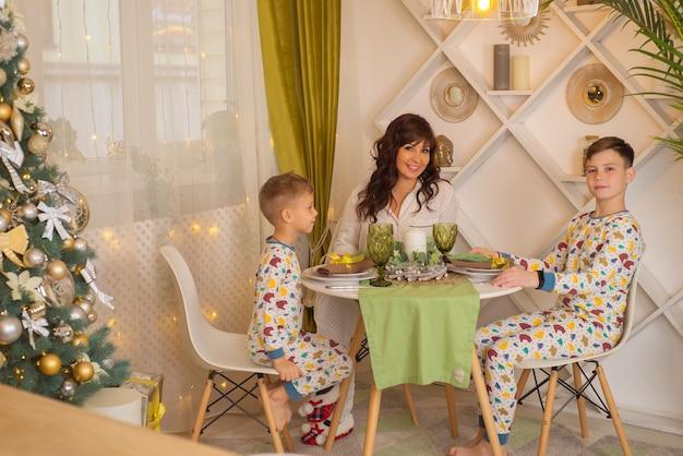 Moeder met kinderen in de keuken samen met kerstmis en gelukkige familie Premium Foto