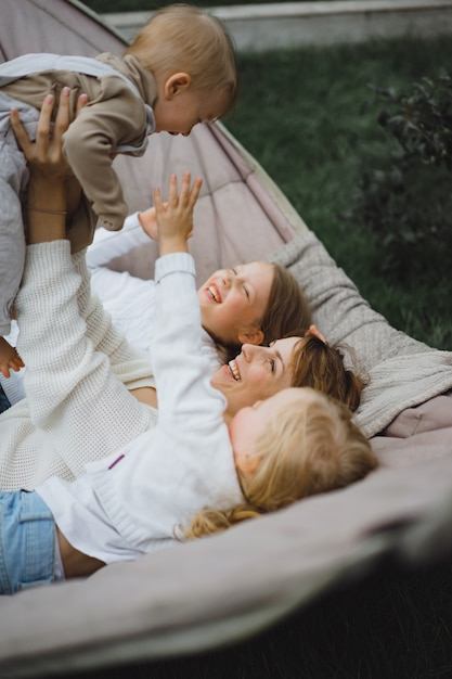 Moeder met kinderen plezier in een hangmat. moeder en kinderen in een hangmat. Gratis Foto