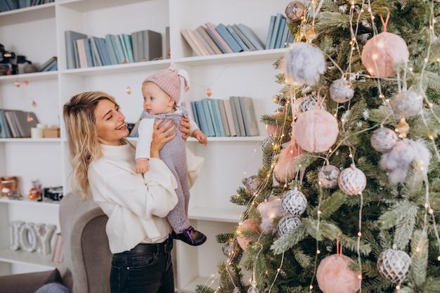 Moeder met kleine dochter bij de kerstboom Gratis Foto