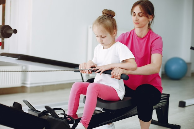 Moeder met kleine dochter houdt zich bezig met gymnastiek in de sportschool Gratis Foto