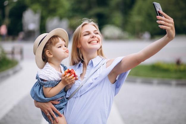 Moeder met kleine dochter in park Gratis Foto