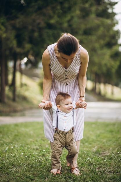 Moeder met kleine peuterzoon in park Gratis Foto