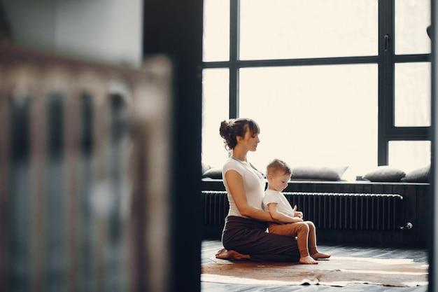 Moeder met kleine zoon die yoga thuis doet Gratis Foto