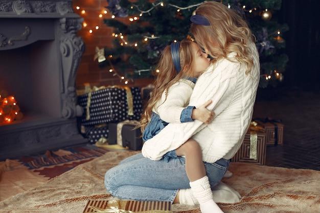 Moeder met schattige dochter thuis in de buurt van open haard Gratis Foto
