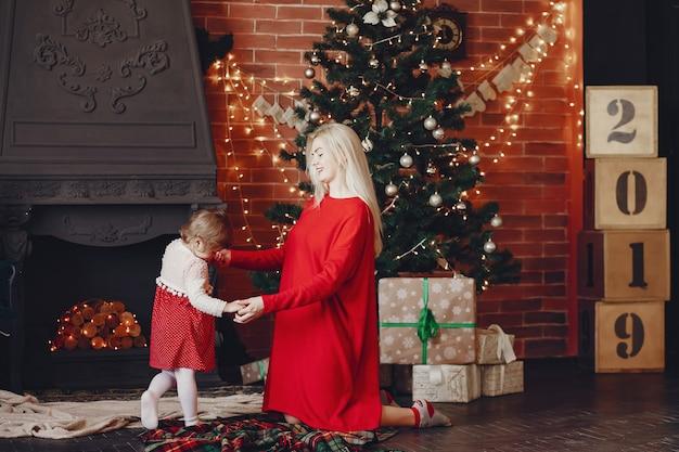 Moeder met schattige dochter thuis in een rode jurk Gratis Foto